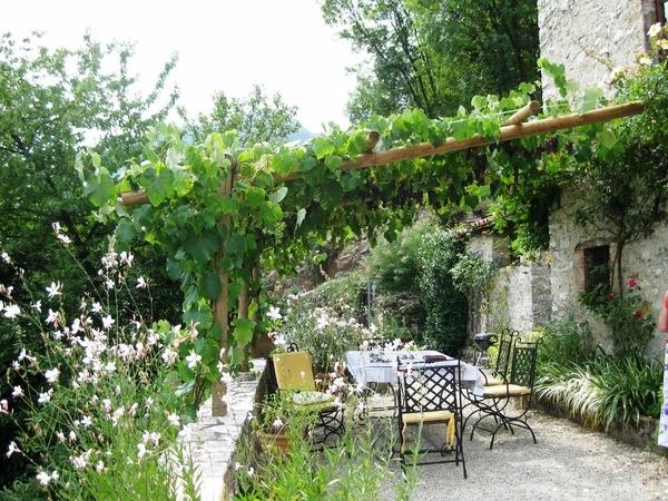 mediterranean-patio-landscaping-outdoor-furniture-sun-protection-wooden-pergola-grapevines