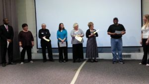 Division B Humorous Speech Contestants (l to r): Kory May, Meg Schneider, Anthony Moschetti, Sherry Sullivan, Michele Ortega, Marilyn McConkey Boyles, and Wilbert Merrick Mitchell. Theresa Mickelson, Division B Director listens as Wilbert responds to her contestant interview question.