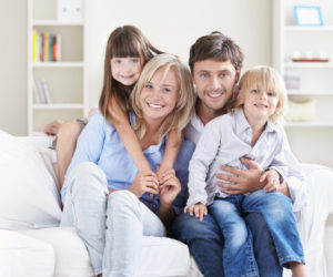 A happy family with children on a white sofa at home