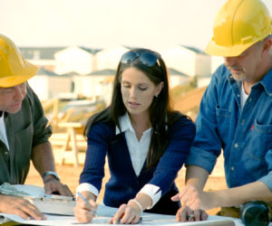 Construction workers look at and discuss plans.