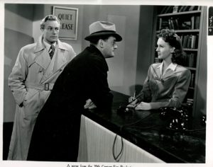 """A still from noir classic """"Quiet Please Murder"""" a librarian regards a detective and his companion askance. Her fall vintage fashion is on point."""