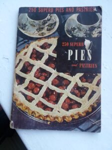 """A worn vintage pie recipe booklet """"250 Superb Pies and Pastries"""" with a cherry pie and two cups of coffee on the cover."""
