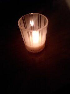A tealight burns in a small striped glass holder, shining in the dark.