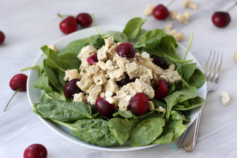 Vegan Cherry Cashew Chicken Salad on top of baby spinach