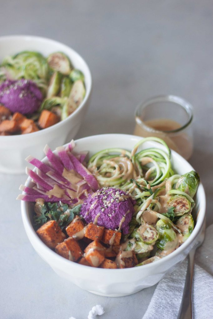 zoodle, purple beet hummus, sweet potato, kale, edamame, brussels, ginger peanut sauce in a bowl