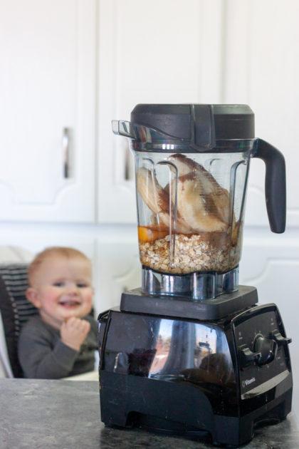 Vitamix blender making banana bread, baby in background