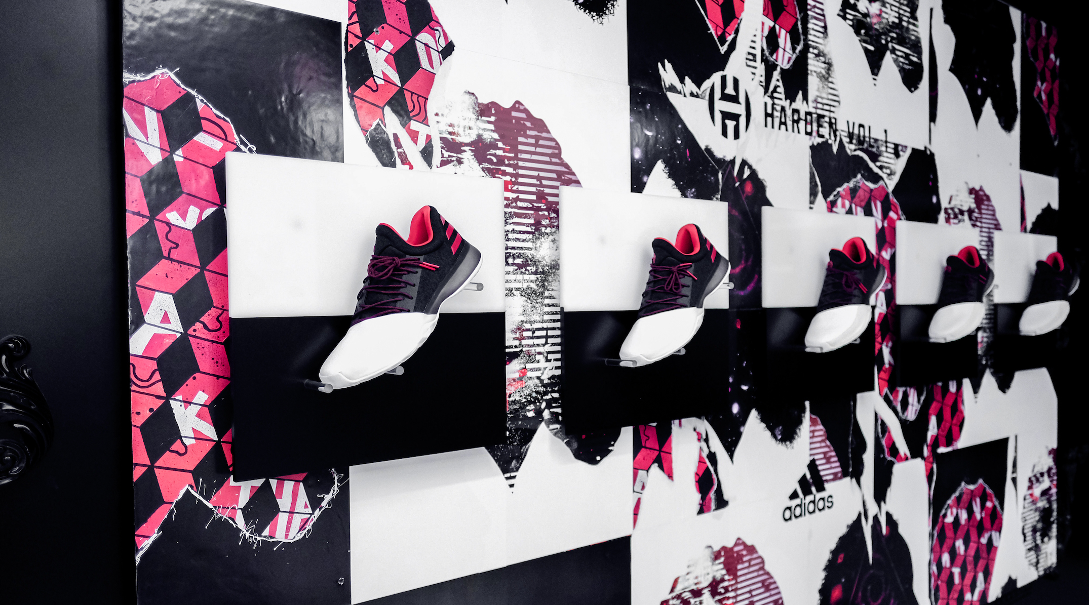 A wall display of Harden Vol. 1 shoes, set at a dynamic angle over squares divided into black and white sections, so the white toes of each shoe align with the black section of the square. All set over textured red, black and white wheatpaste graphics.