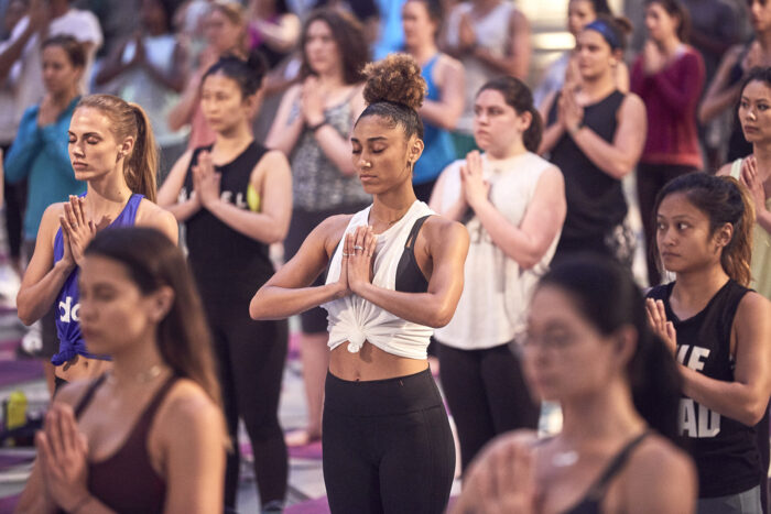 A group of women following a yoga routine stand with hands to heart.