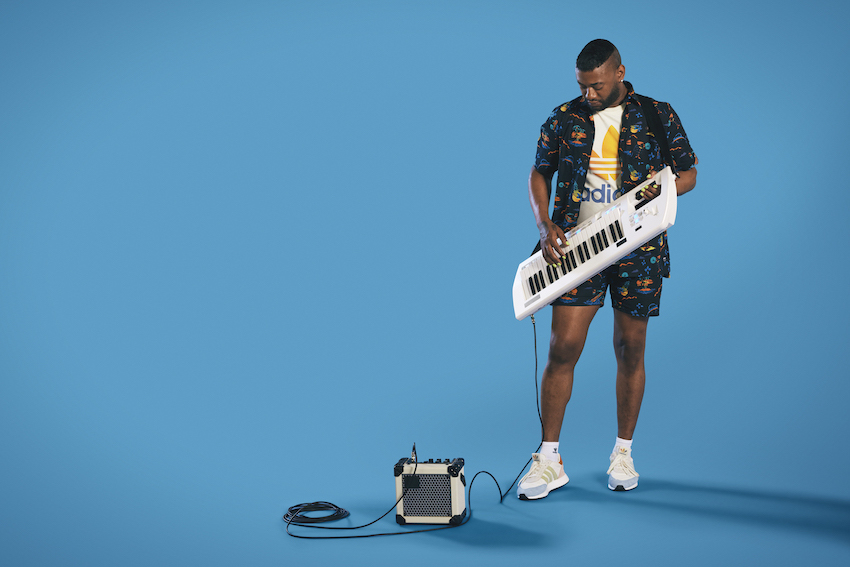 Chanti Darling holds an electric keyboard plugged into an amp, standing in a blue space.