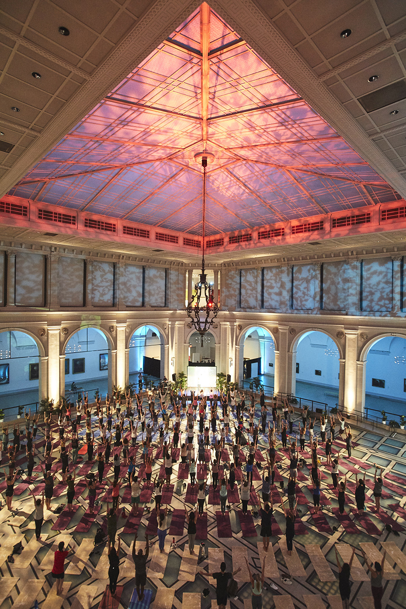 A view of the atrium full of participants doing yoga, the space is gently lit in blue and pink.