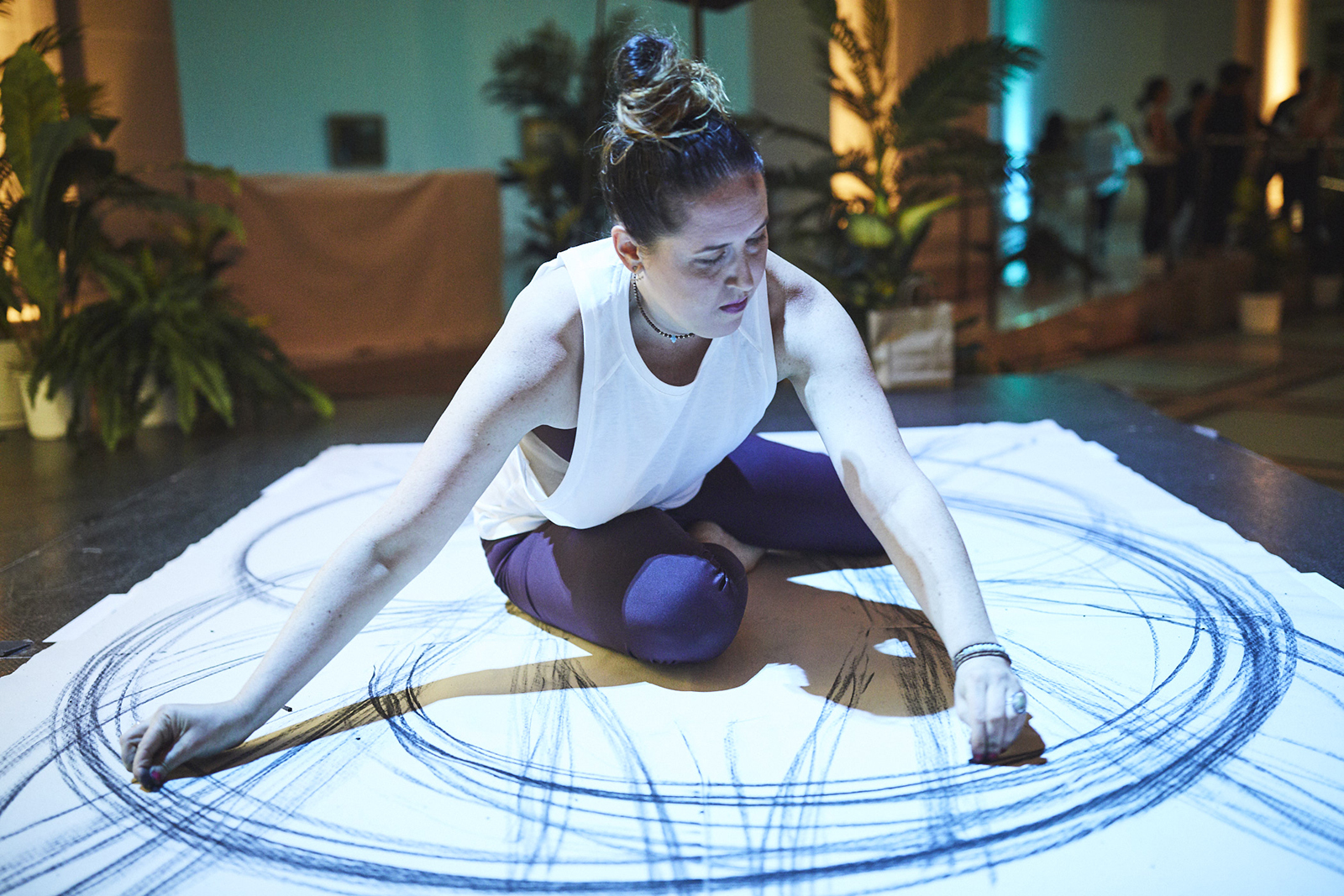 A woman practices meditative gestural drawing while sitting atop a large piece of paper, drawing large sweeping circles of charcoal around her body.