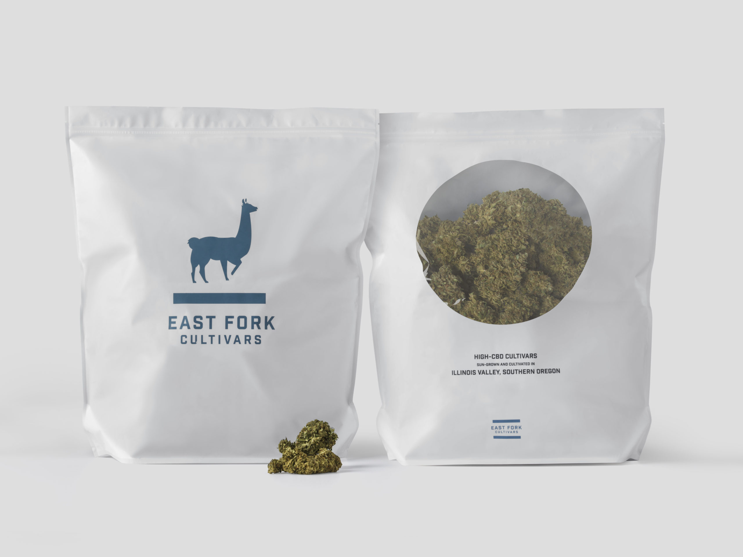 Two white bags of East Fork Cultivars High-CBD flowers, side by side, showing front and back. The left bag shows the blue East Fork Cultivars llama logo, the right a circle cutout window displaying the flower product inside the bag.