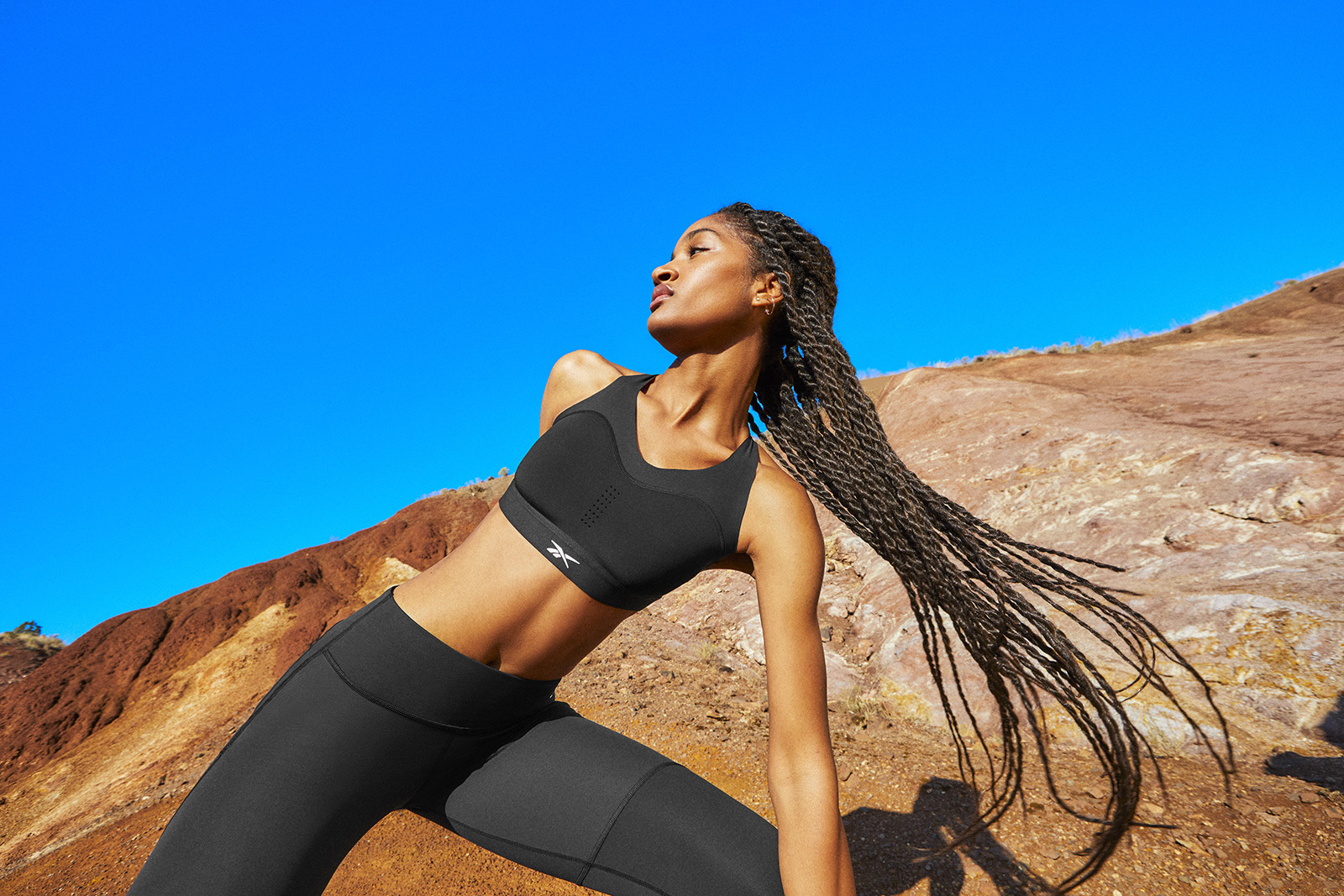 Woman wearing black bra and tights stretches in the same red earth, blue sky location.