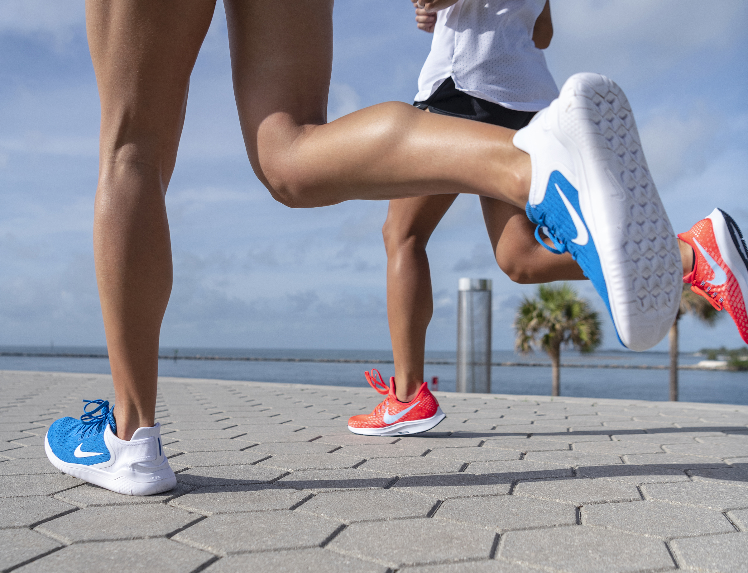 A close up on the legs of two runners wearing Nike, mid-stride, as they run along the water.