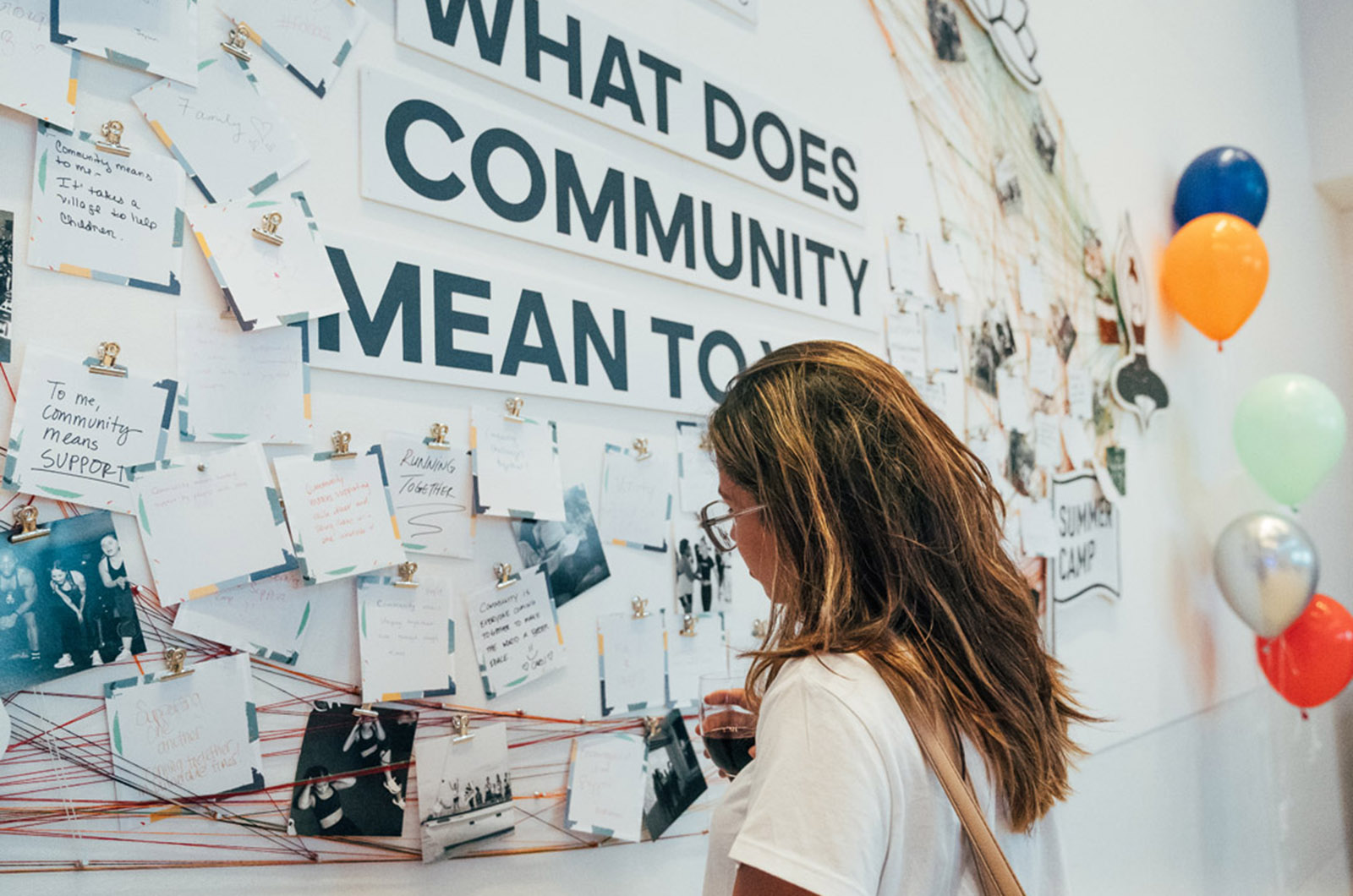 A woman looks at a wall of notes and images clipped to strings around a sign that reads: What Does Community Mean To You?