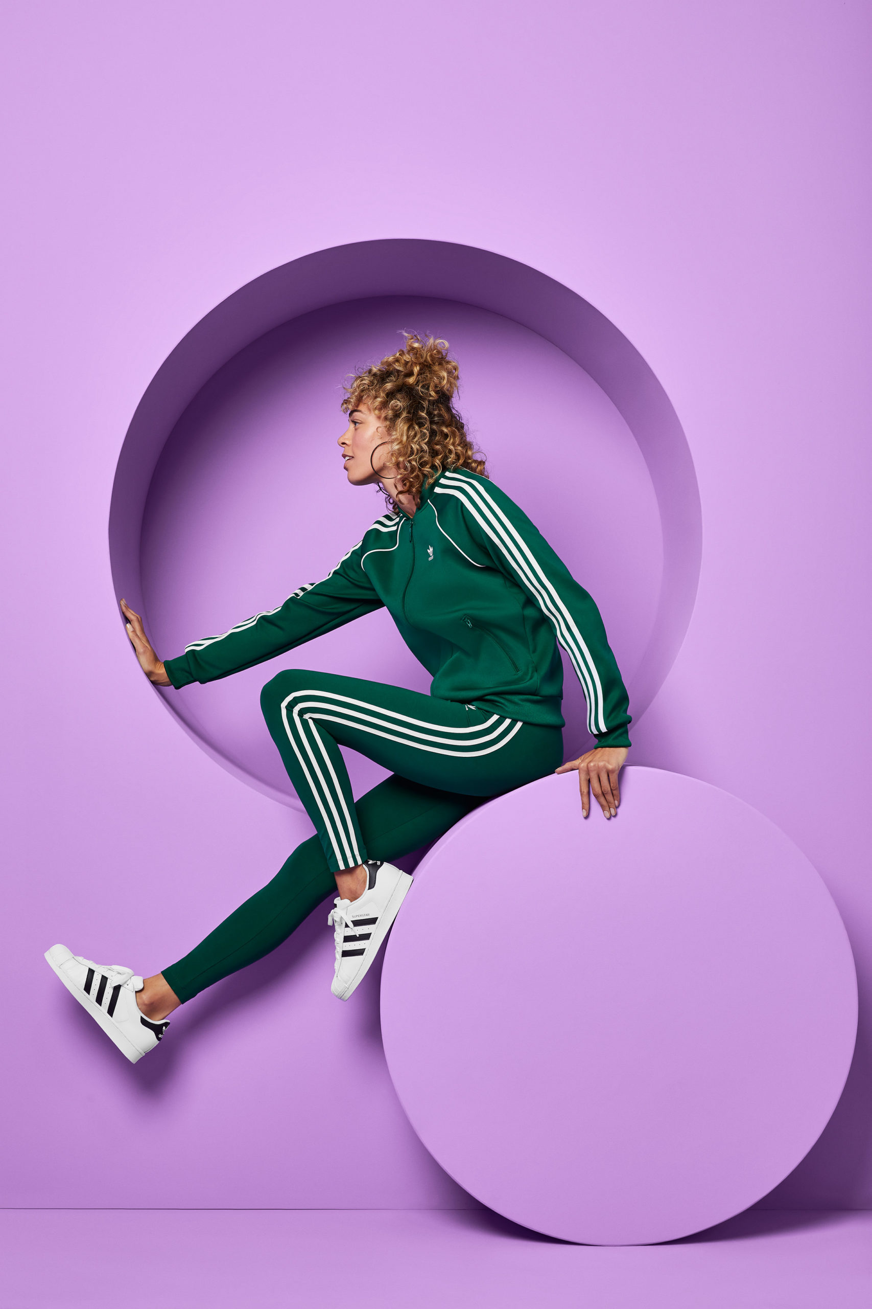 A woman in a green jacket and tights sits on a round set piece against a lavender set.