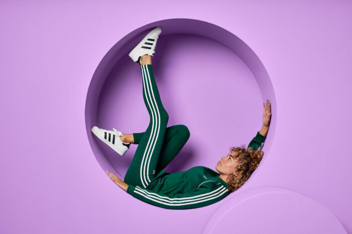 Woman wearing all emerald green reclines in a circular cutout in a lavender-purple wall.