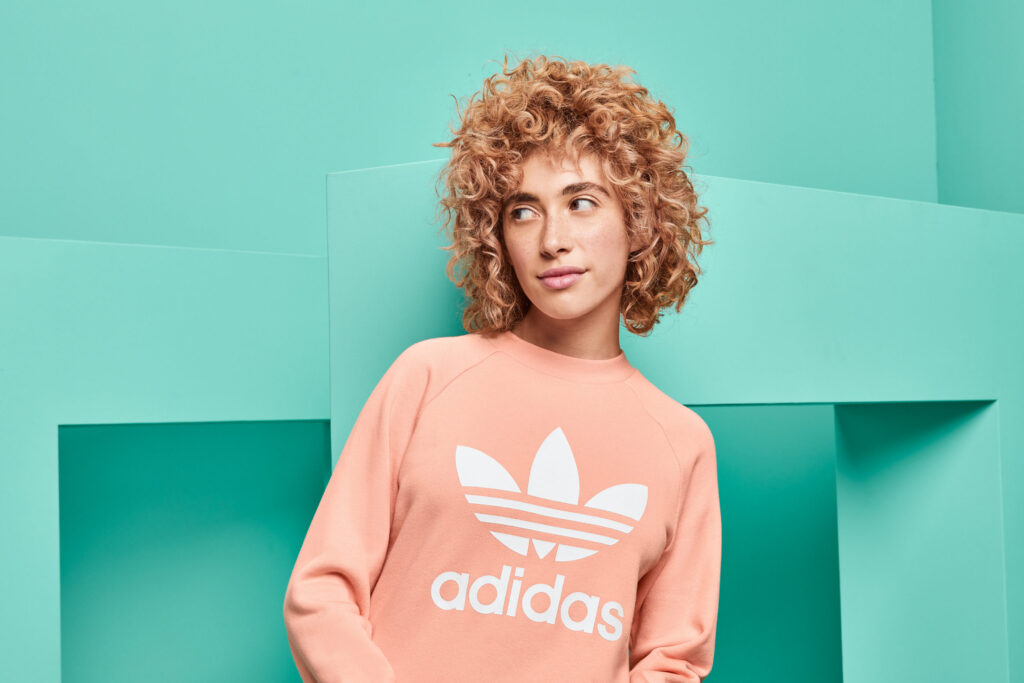A woman wearing a pink sweatshirt stands against a seafoam green set with rectangular arches.