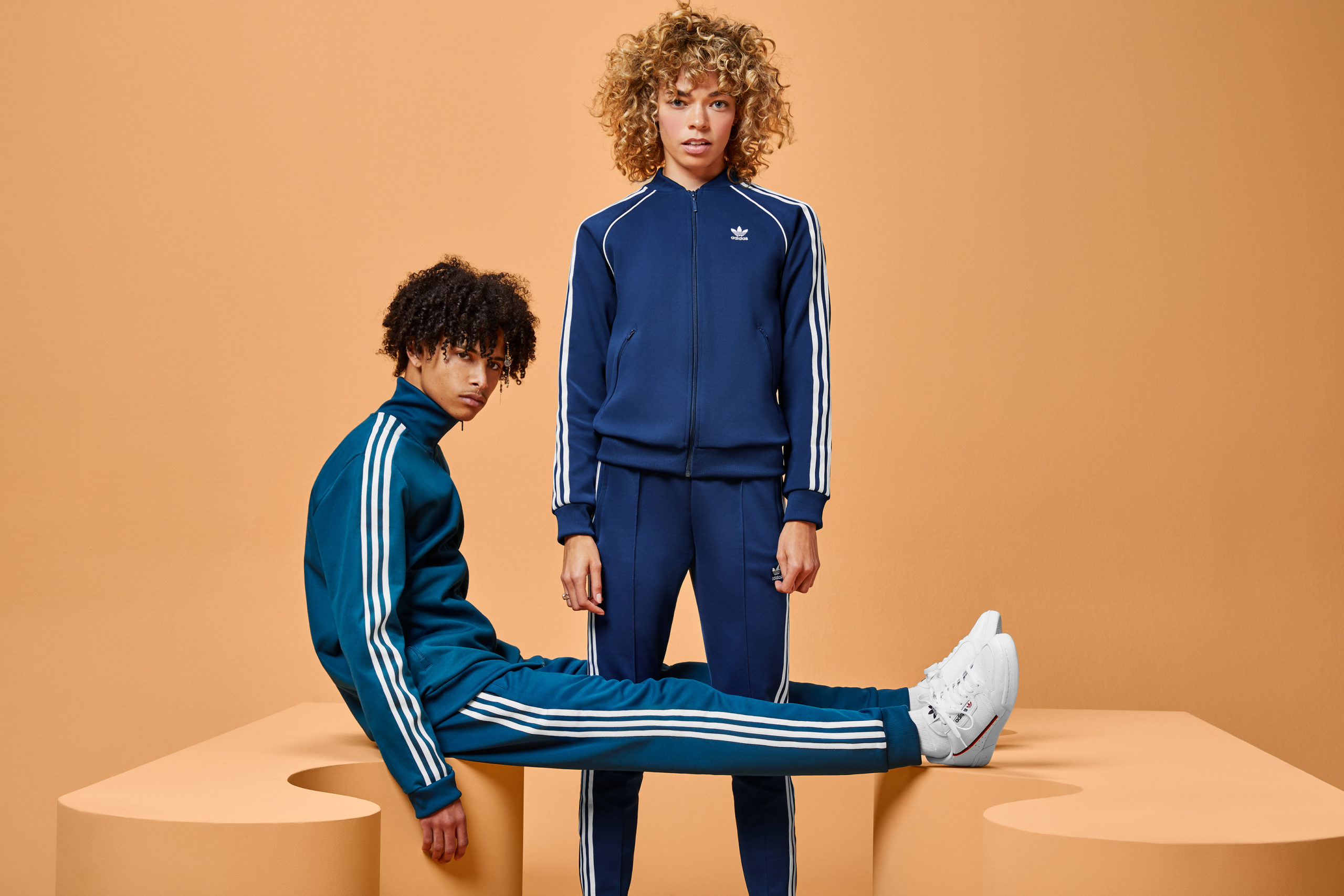 A woman wearing a blue tracksuit stands between the legs of a guy, also wearing a blue tracksuit, who's sitting on a wavy modular shape with legs propped up on another wavy shape. Both shapes and the background are an orange-tan.