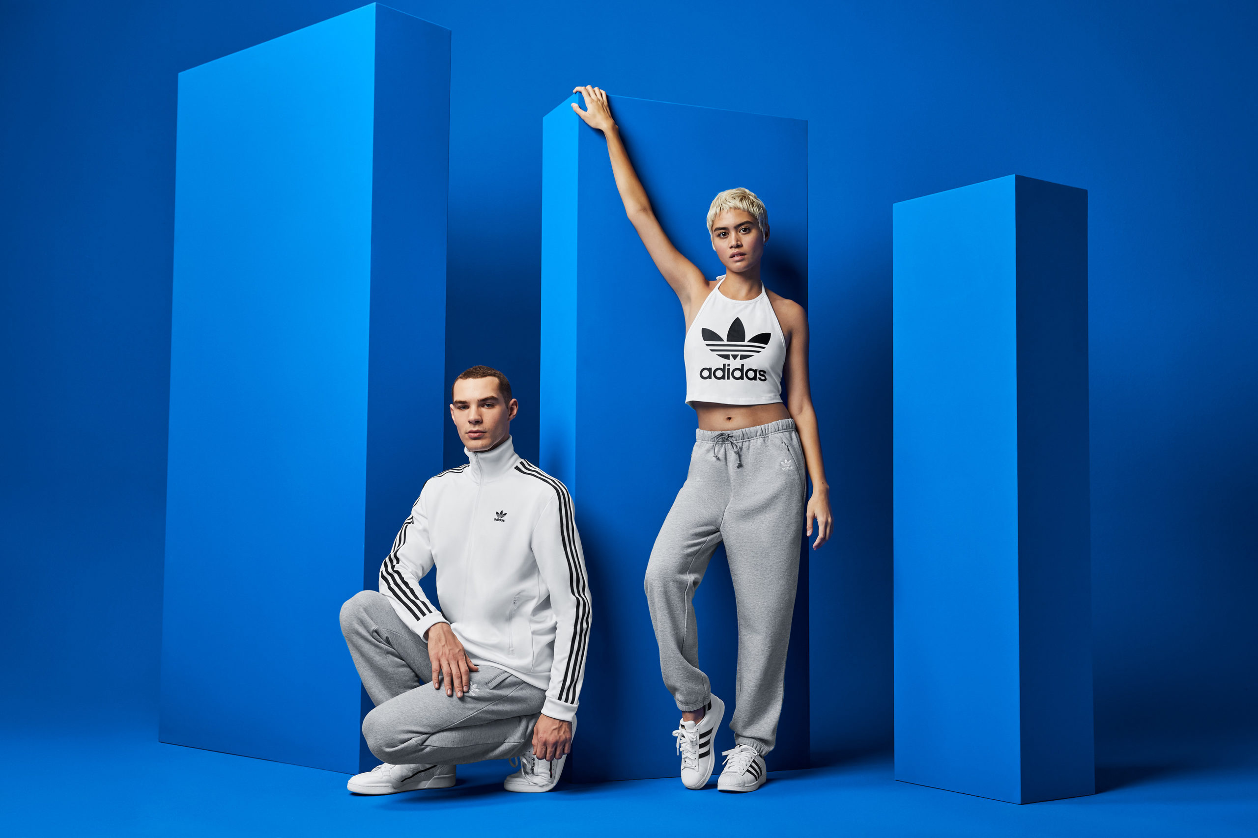 Two models, in white and gray, kneel and stand in a blue set in front of three blue modular towers.