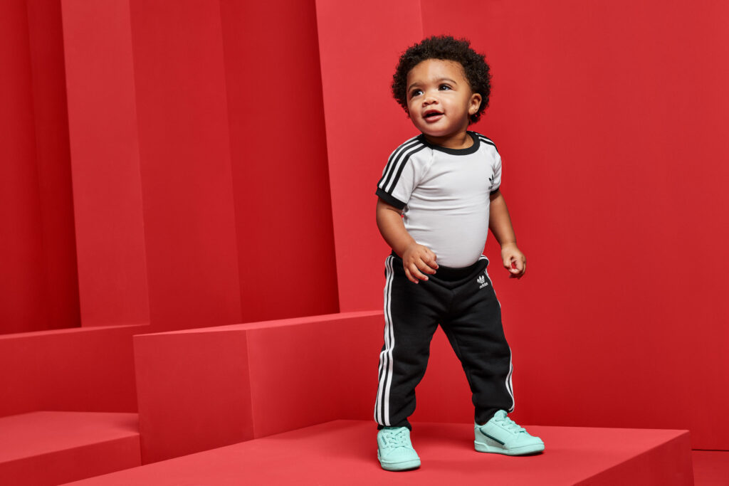 A toddler wearing black and white stands in a red set.
