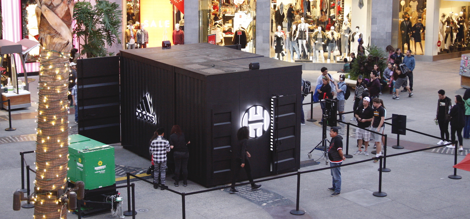 An aerial view of the activation pod which is a large black shipping container with large lit adidas and Harden logos, and a door cracked open to reveal a black and white striped glowing interior.