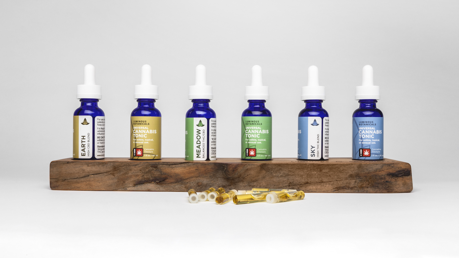Six bottles of cannabis tonic displayed so two sides of each label can be seen. Each label has the product name listed horizontally over a color field, and the blend vertically over a white column.