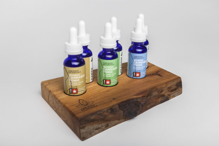 Bottles of cannabis tonic displayed on a piece of wood.