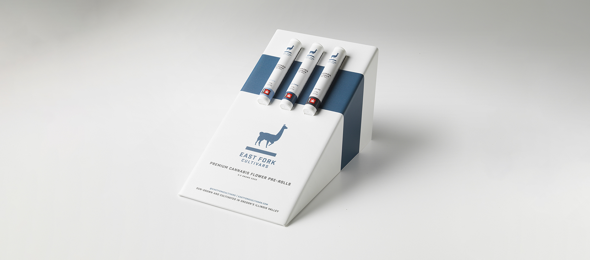 A blue and white angled display box of three East Fork pre-rolls, Create, Balance, and Relax strains.