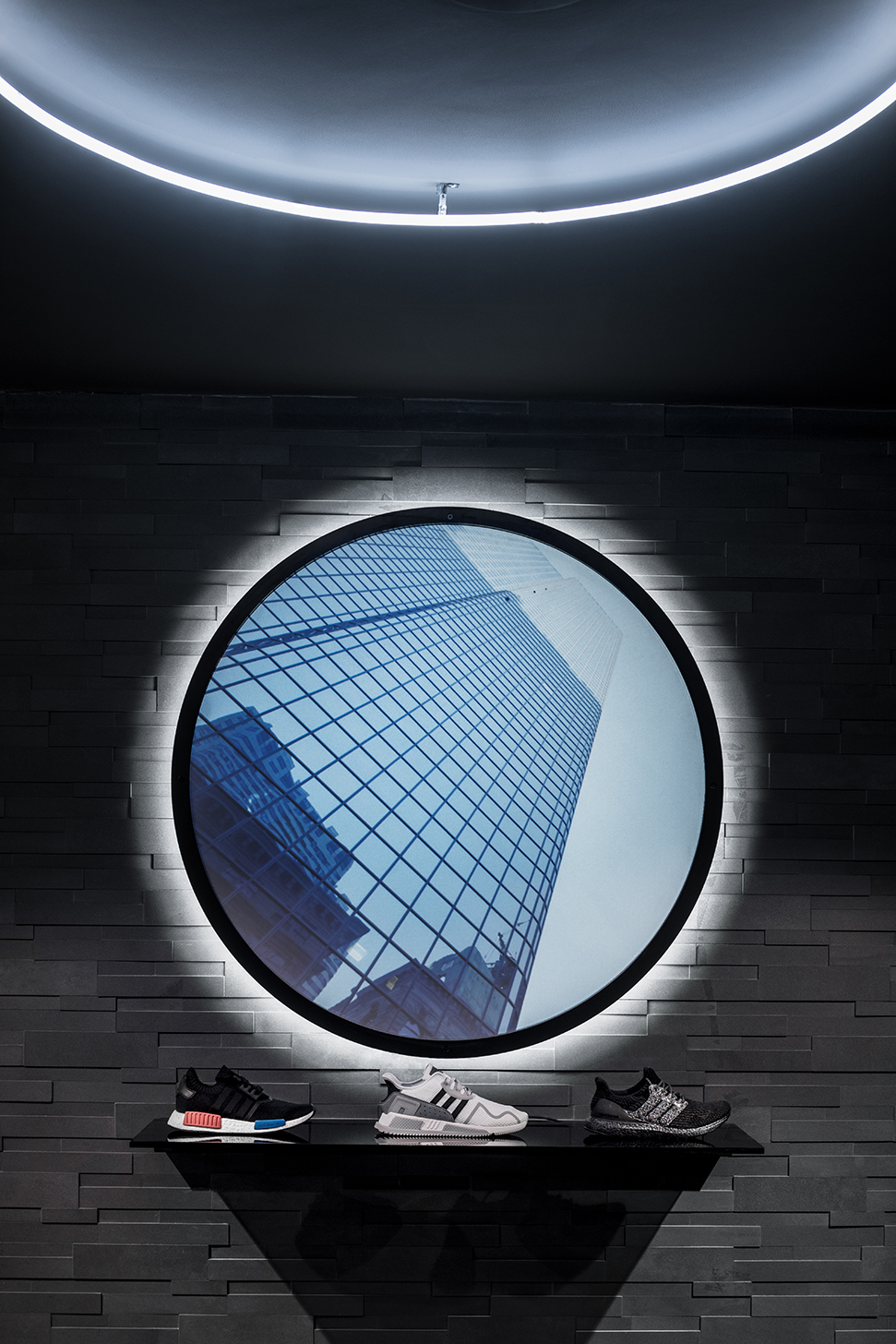 Three shoes on a shelf below a halo ring of neon and the Shrine, a circular projection screen showing a building as seen from below.