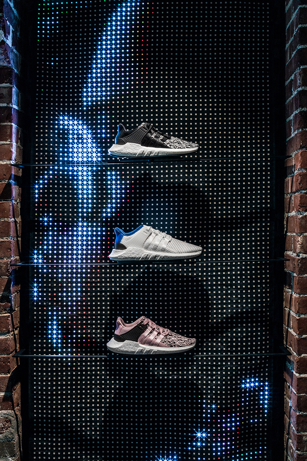 A closeup of three sneakers posted in front of a profile of a face shown on the LED curtain.