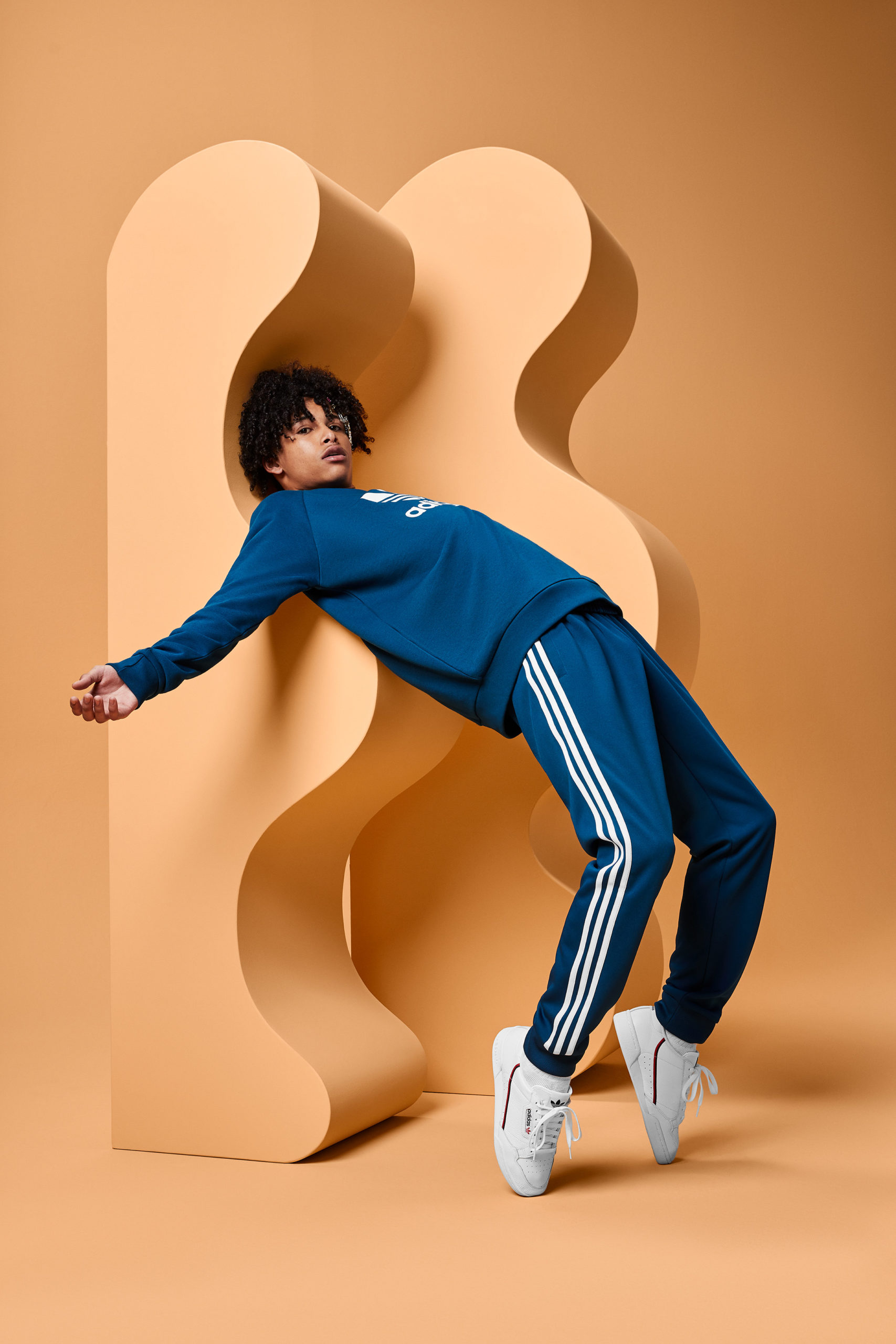 A guy in blue sweats leans back on tip-toes against a tan squiggly-shaped modular piece on a tan set.