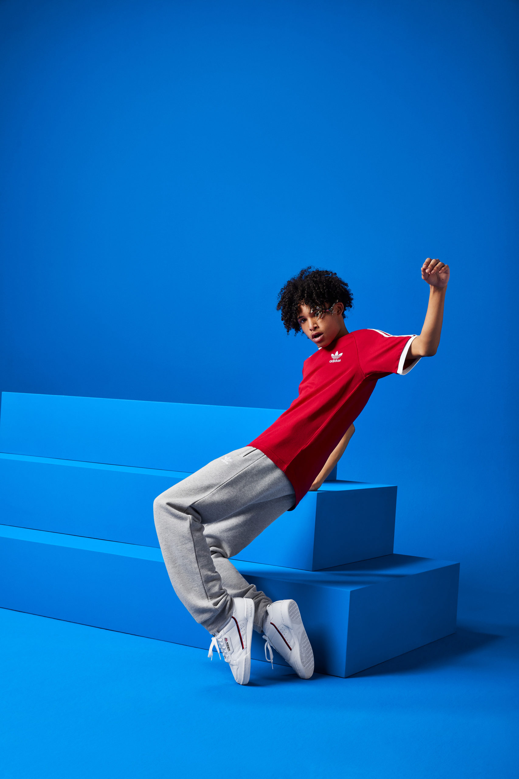 A guy wearing a red shirt dances in front of a blue set with a stack of stair-stepped boxes.