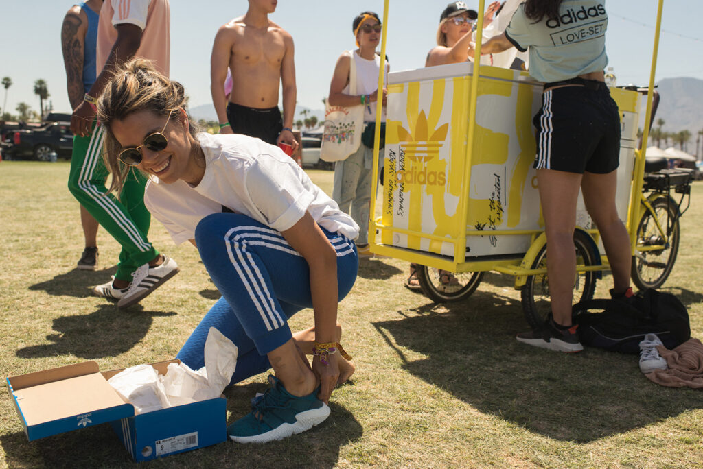 Someone kneels down to try on a sneaker, all smiles, while a few people behind them get gear being handed out from a yellow ice cream-style cart.