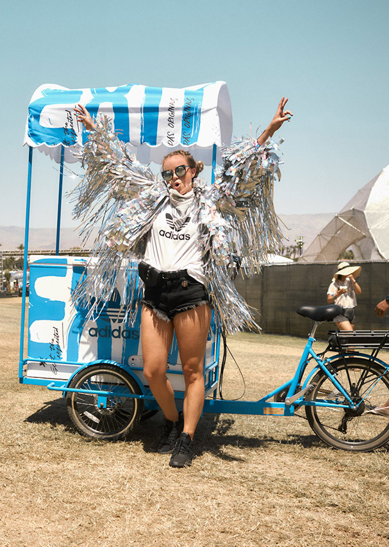 A woman in a silver fringe jacket, adidas tee, and cutoff shorts stands with arms raised in front of a bike mounted, canopy covered ice-cream-style cart branded in blue EXIT graphics and a big trefoil logo.