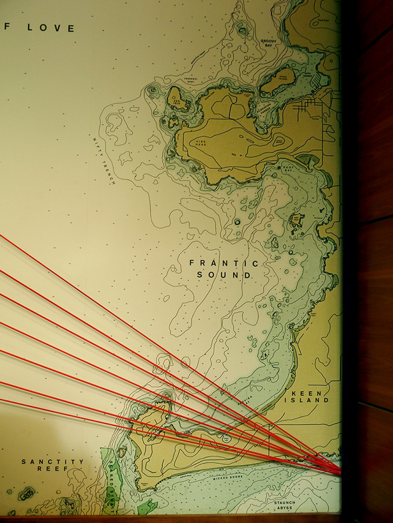 One of the wall maps features locations around Frantic Sound, including Nifty Trench, Keen Island, Sanctity Reef, and Wicked Shore. Seven orange cords fan over top, angled so they meet at a point on the right side.