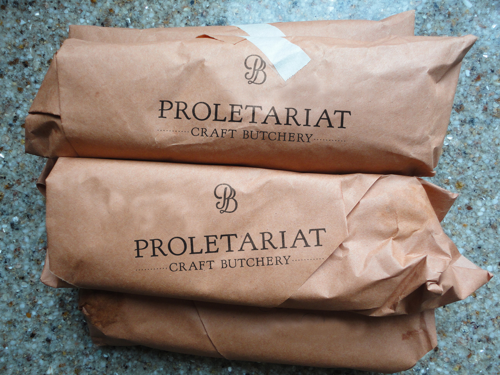 Cuts of meat wrapped in branded butcher paper, featuring a PB logomark and horizontal Proletariat type treatment.