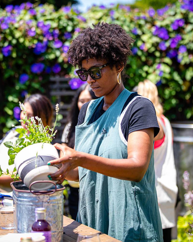 A woman plants an herb in a pot at an adidas Women's event.