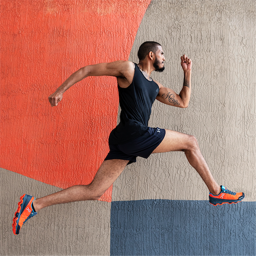 A man running, mid-stride and fully airborne, in front of a wall the same colors as his shoes.