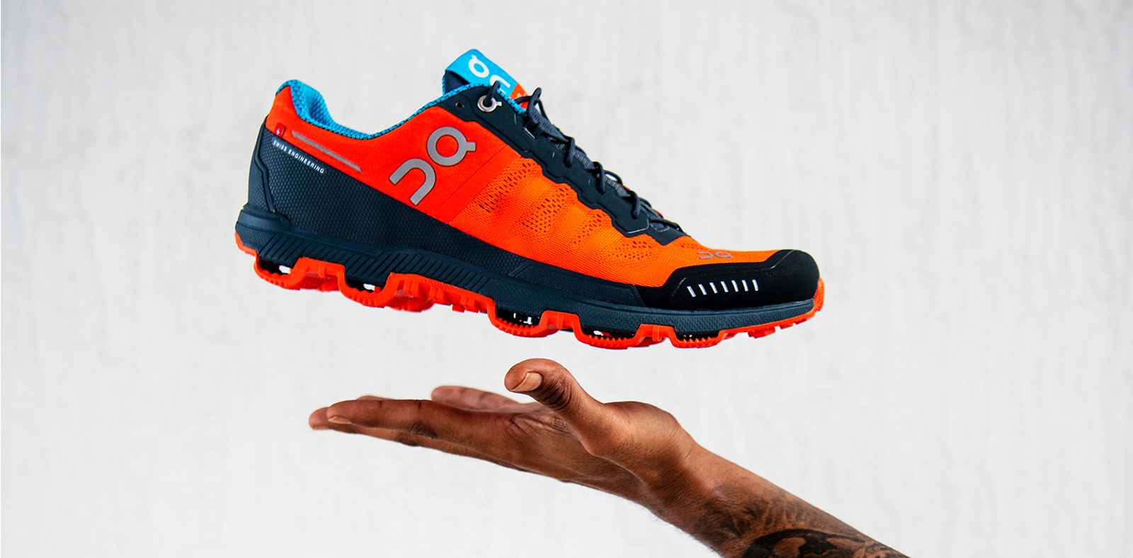 An orange, black, and blue On shoe floats above a hand.
