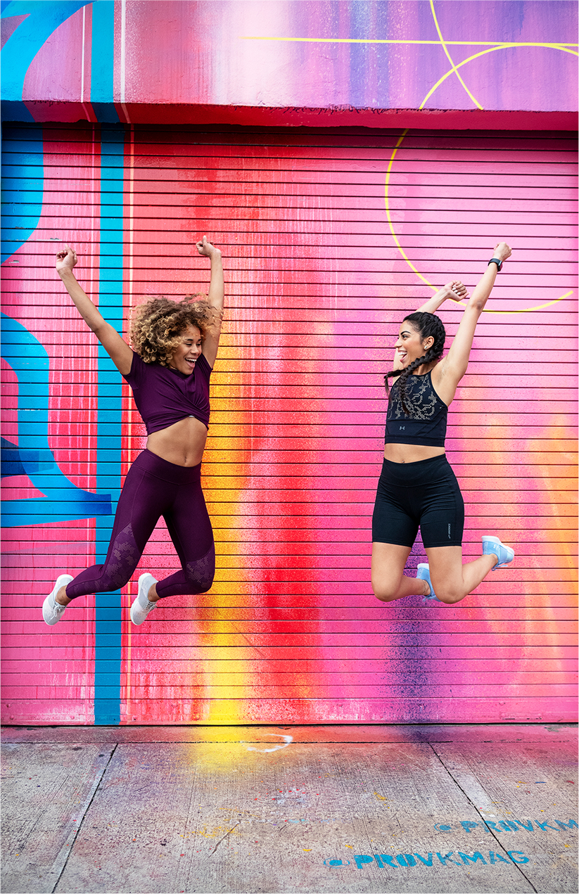 Two women joyfully jump in front of a colorful wall.