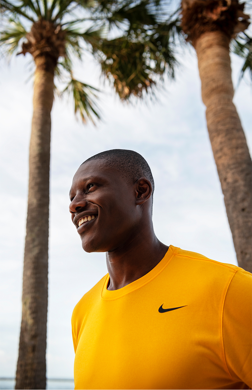 A man in a Nike shirt smiles under a couple palm trees.