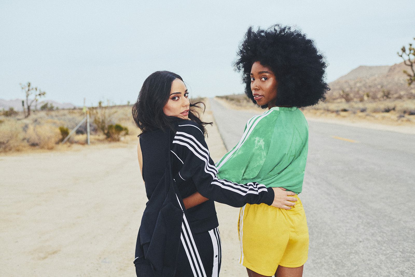 Two women, one in all black with her track jacket hanging off one shoulder and the other in bright green and yellow adidas gear stand on the side of a desert road with arms around each other's waists, looking over their shoulders.