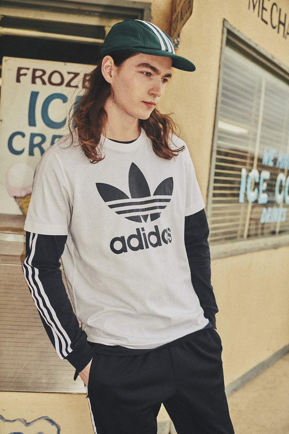 A guy wearing an adidas tee over a long sleeve and a cap with three stripes stares off into the distance, standing with his hands in his pockets in front of a sign for ice cream.