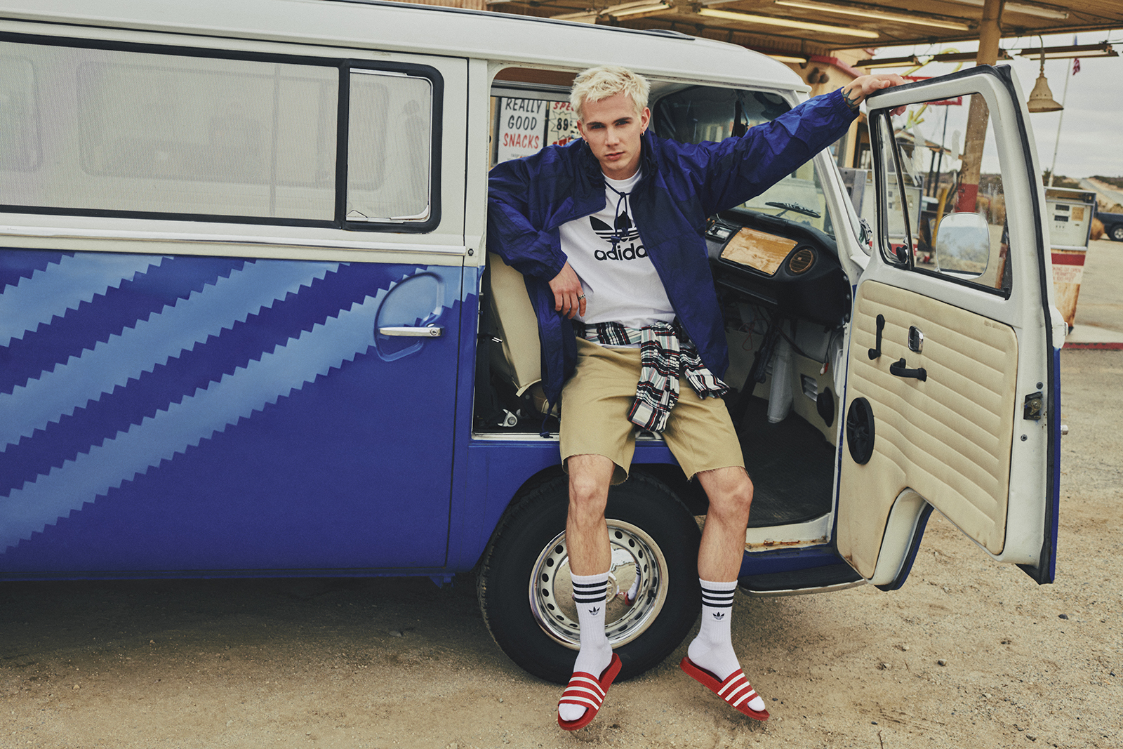 A guy wearing a blue windbreaker, adidas tee, socks, and slides leans in the open door on the passenger side of an Originals themed Volkswagen bus parked in a desert gas station.