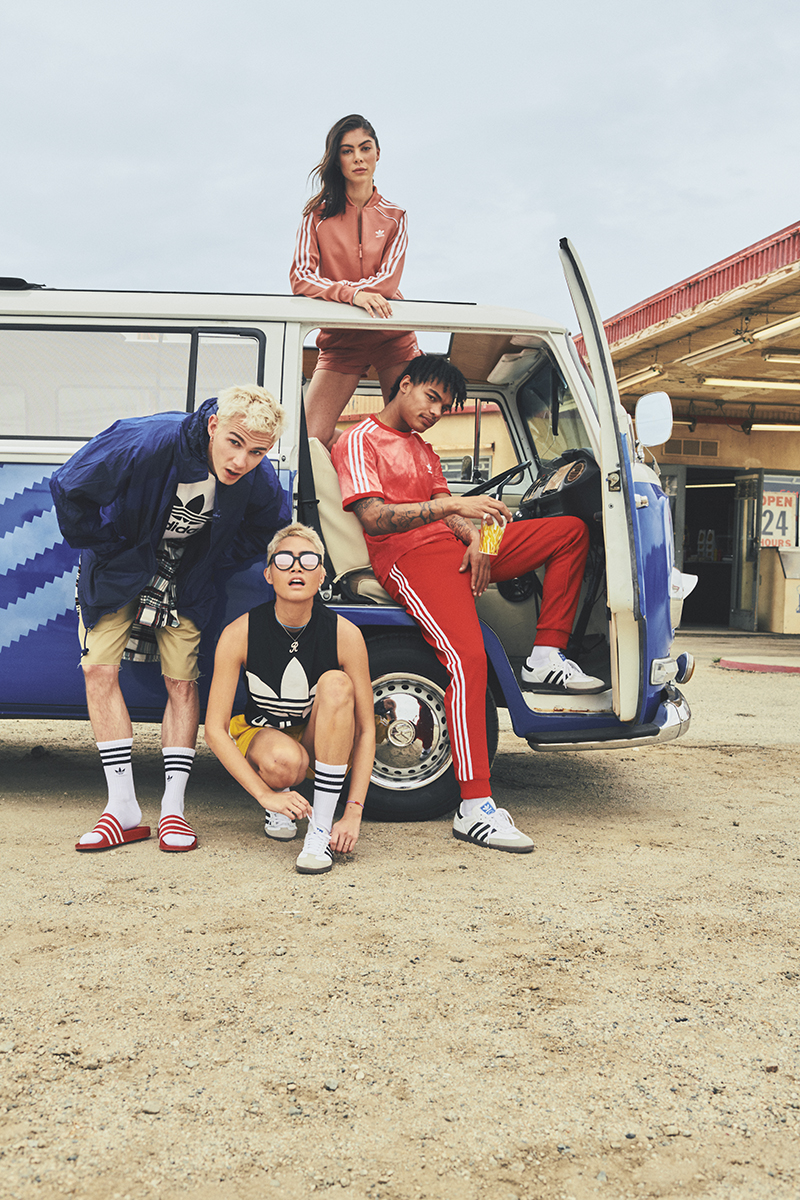 A group of four people, decked out in adidas gear, pose in and around the adidas Originals VW bus.