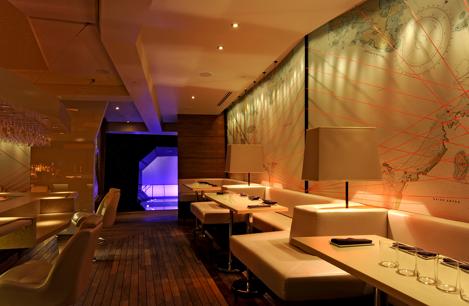 The dining room with light-colored leather booths, dark wood, and the fanciful nautical maps filling the walls.