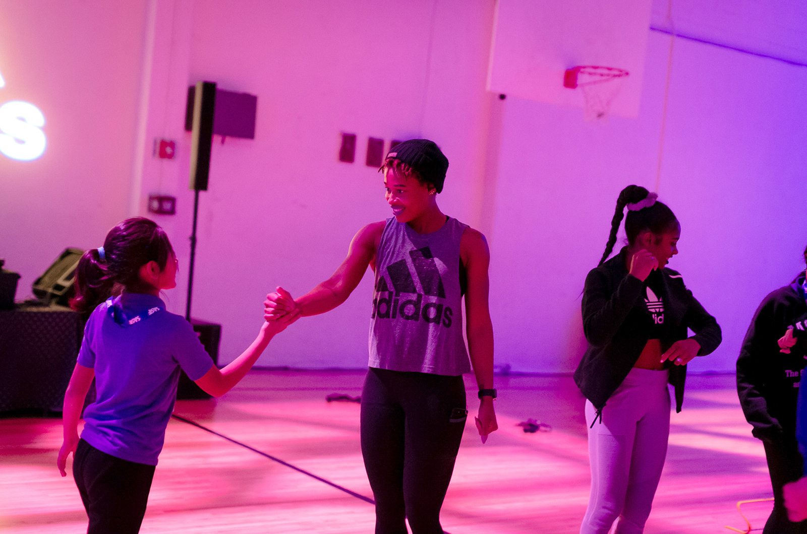 Girls shake hands at an event in a gym.