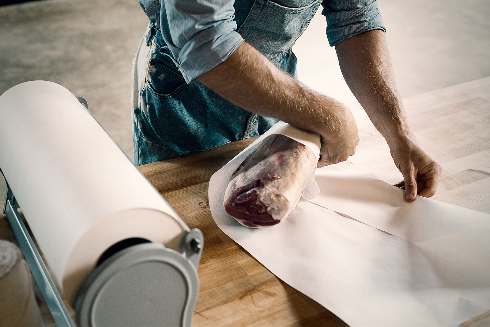 A cut of meat is being wrapped in butcher paper.