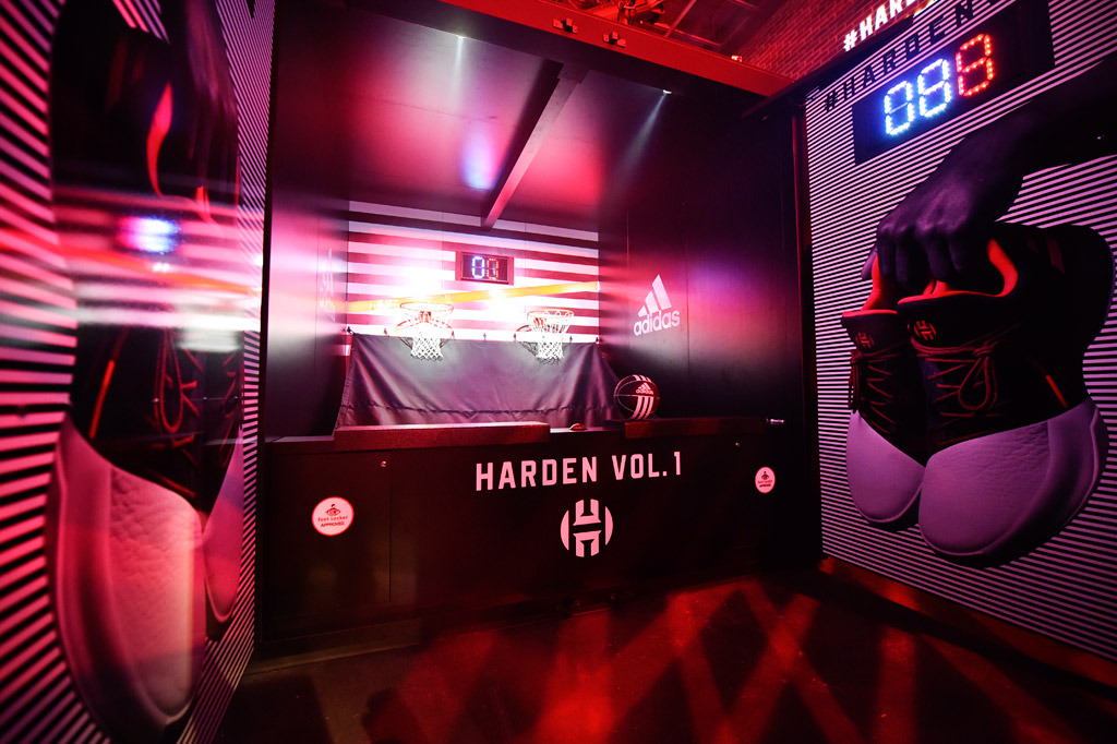 A view of the pop-a-shot game customized with adidas and Harden branding, and immersive black and white striped wall graphics showing a hand holding a pair of the shoes.